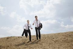 Two young businessmen running and exhausted in the desert, holding jackets - stock photo