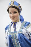 Portrait of young smiling woman in traditional clothing from Russia, studio shot - stock photo