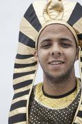 Stock Photo of Portrait of smiling young man wearing a headdress from ancient Egypt, studio