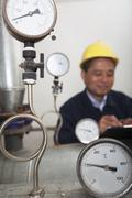 Close- up on gas gauges with worker in the background in a gas plant, Beijing, - stock photo