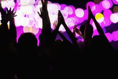 Audience watching a rock show, hands in the air, rear view, stage lights - stock photo