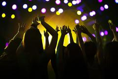 Stock Photo of Audience watching a rock show, hands in the air, rear view, stage lights
