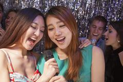 Group of friends singing into a microphone at karaoke Stock Photos