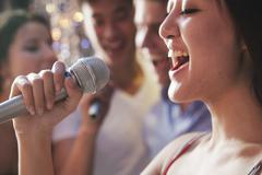 Close- up of young woman holding a microphone and singing at karaoke, friends - stock photo