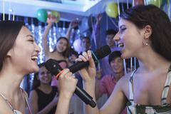 Two friends holding microphones and singing together at karaoke, face to face, - stock photo