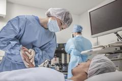 Surgeon consulting a patient, holding hands, getting ready for surgery - stock photo