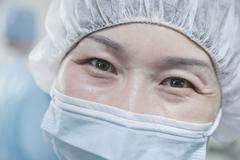Stock Photo of Portrait of surgeon with surgical mask and surgical cap in the operating room