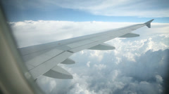 Stock Video Footage of Airplane wing while flying over cloudscape
