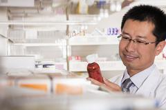 Pharmacist taking down and examining prescription medication in a pharmacy Stock Photos