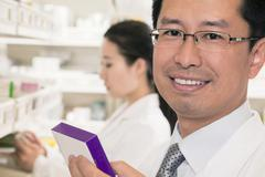 Portrait of smiling pharmacist holding prescription medication and looking at Stock Photos