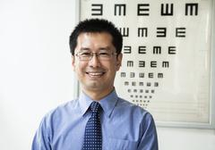 Portrait of smiling optometrist with an eye chart in the background - stock photo