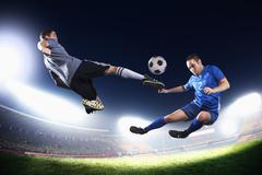 Two soccer players in mid air kicking the soccer ball, stadium lights at night Kuvituskuvat