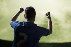 Soccer player with arms raised cheering, stadium with green sky Stock Photos