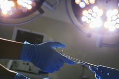 Close-up of gloved hands passing the surgical scissors, operating room, hospital Stock Photos