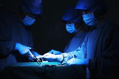 Team of surgeons holding surgical equipment at the operating table and working Stock Photos