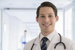 Portrait of young doctor in lab coat in the hospital, looking at camera, Stock Photos