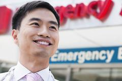 Portrait of smiling doctor outside of the hospital, emergency room sign in the - stock photo