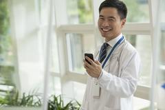 Smiling doctor using his phone in the hospital lobby, looking at camera, glass Stock Photos