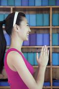 Portrait of young women doing yoga with hands clasped together, side view Stock Photos
