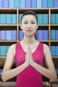 Portrait of young women doing yoga with hands clasped together, looking at - stock photo