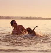 man with little beagle puppy fooling around in ocean sunset waves - stock photo