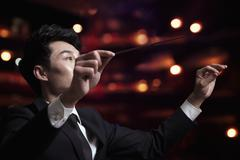 Young conductor with baton raised at a performance Stock Photos