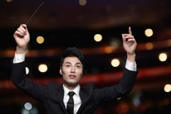 Young conductor with baton raised at a performance - stock photo