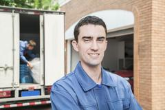 Portrait of smiling mover with moving truck in the background Stock Photos