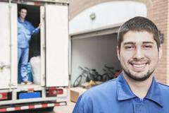 Portrait of smiling mover with moving truck in the background - stock photo