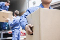 Movers unloading a moving van - stock photo