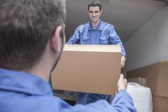 Movers unloading a moving van, passing a cardboard box - stock photo