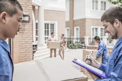 Mover holding clipboard and invoice, family in the background - stock photo
