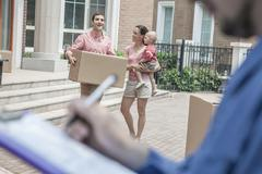 Mover holding clipboard and invoice, family in the background Stock Photos