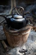 Stock Photo of old used kettle on tradition stove with water stream