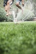 Two people jumping through a sprinkler, mid-air, surface level shot Stock Photos
