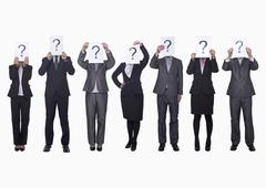 Medium group of business people in a row holding up paper with question mark, - stock photo