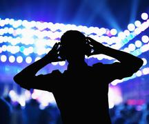 Silhouette of DJ wearing headphones and performing at a night club - stock photo