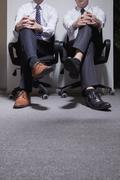 Two businessmen sitting down with legs crossed, low section - stock photo
