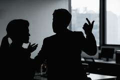 Silhouette of two business people gesturing and arguing in the office Stock Photos