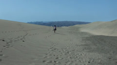 Following a Girl between Dunes and Desert Sand in Maspolamas Stock Footage