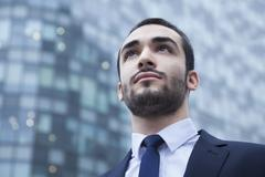 Stock Photo of Portrait of serious young businessman looking up, outdoors, business district