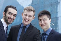 Portrait of three smiling businessmen, outdoors, business district - stock photo