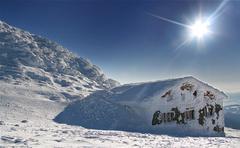 Fairy tale building in wintertime with sun - kamenna chata Stock Photos
