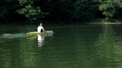 Man with sunglases kayaking in lake by a forest Stock Footage