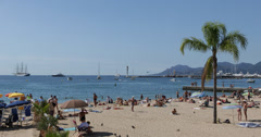 Ultra HD 4K French Riviera People sunbathing swimming beach umbrella Cannes Stock Footage