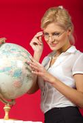 pretty woman teacher with globe - stock photo