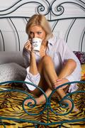 Young woman drinking coffee on the bed Stock Photos