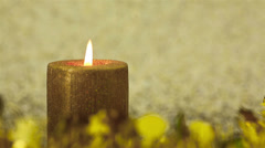 Christmas candle burning on golden background Stock Footage