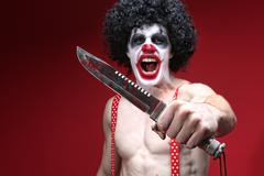 Stock Photo of spooky clown holding a bloody knife