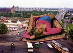 girl on the rug over city - stock photo